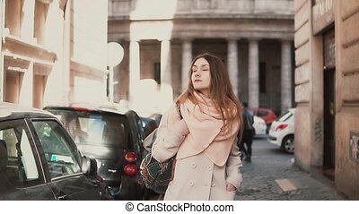 Portrait of young stylish woman walking in the city centre....