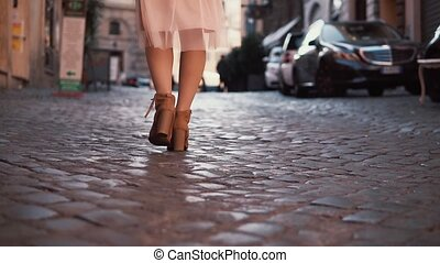 Woman walking on cobblestone pavement road. Girl exploring...