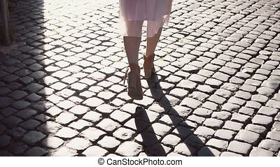 Back view of young woman walking in city centre in streets...
