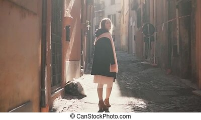 Portrait of young stylish woman walking in the alley, side...