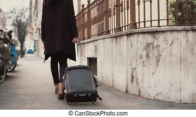 Traveler woman legs walking carrying a suitcase in a city street. Girl come on vacation in Europe.