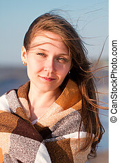 Close up of a young smiling woman covered with blanket at the beach