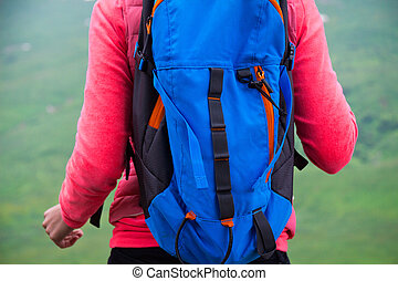 Young Woman Traveler with Backpack hiking in Mountains with beautiful summer landscape on background mountaineering sport lifestyle concept, close up