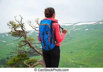 Young Woman Traveler with Backpack hiking in Mountains with beautiful summer landscape on background mountaineering sport lifestyle concept