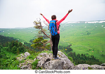 Happy woman hiker with her arms outstretched, freedom and happiness, achievement in mountains