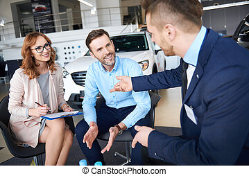 Woman signing the papers in the car dealership