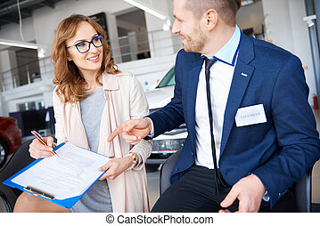 Attractive woman signing necessary documents