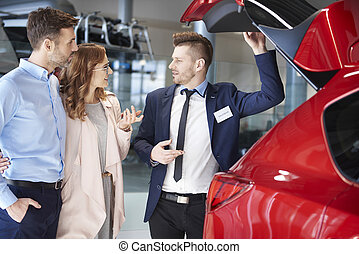 Salesman showing couple the car trunk