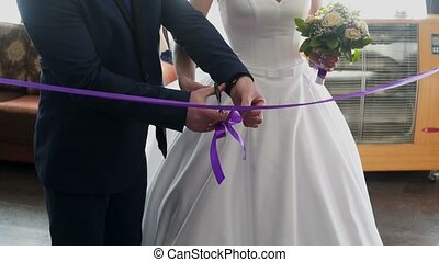 Bride and groom cutting violet ribbon at the party