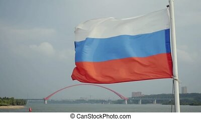 Russian flag blowing with bugrinskiy bridge in the...