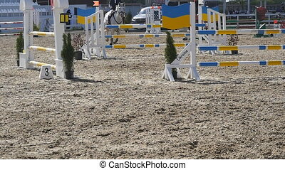 Horse runs and jumps through a barrier at sport competition....