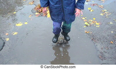 Happy little boy jumping in muddy puddle, slow motion