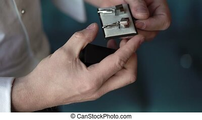 Man takes cufflinks from a box closeup