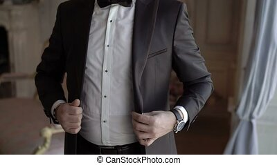 Man wears jacket and buttoning