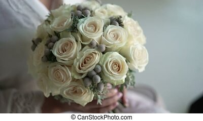 Young unrecognizable woman with bridal bouquet with white...