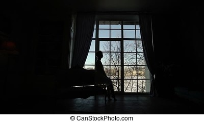 Young strong woman posing near window silhouette
