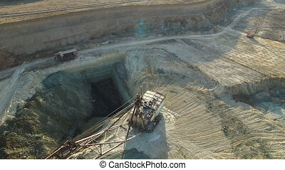 Flying over the iron ore quarry. Excavator digs for iron ore...