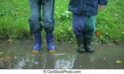 Two boys jumping in muddy puddle together, slow motion