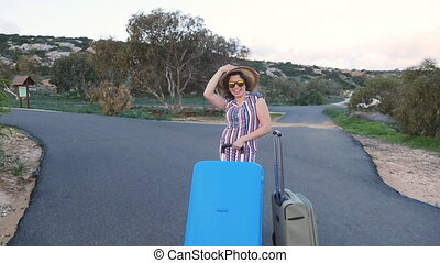 Happy young woman traveler with suitcase. Travel concept