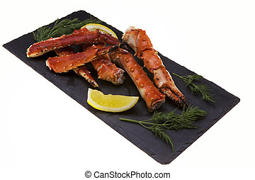 Boiled crab legs with lemon slices and dill on black plate...