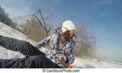 Happy young cute woman is sledding in the mountain through...