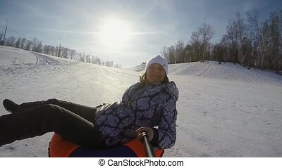 Happy young pretty woman is sledding in the mountain through...