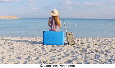 Young woman traveler sits on the beach with a suitcase....