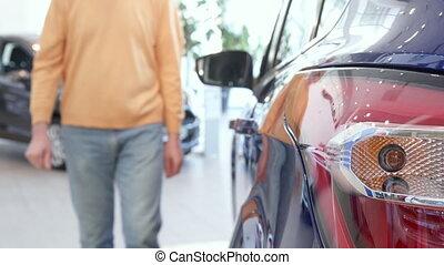 Man opens rear door of purple crossover - Senior man opening...