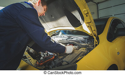 Mechanic in car repairing service - diagnostics in engine...