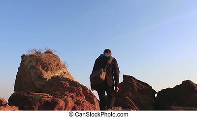 Man standing on stones against the sky