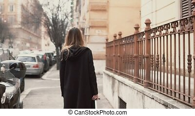 Young woman in black coat walking in the old town part. Back view of the girl exploring the new city. Slow motion.