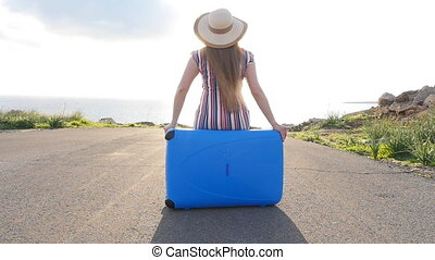 Traveler woman sitting on her suitcase