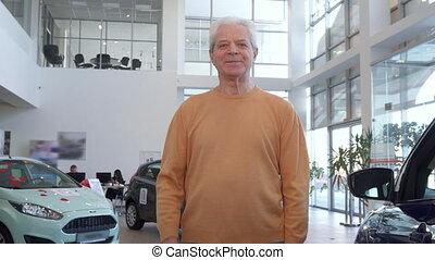 Senior man shows car key at the dealership - Gray senior man...