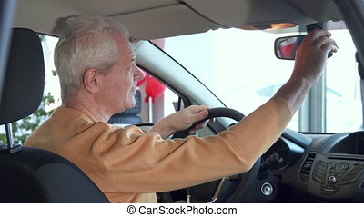 Senior man adjusts rear-view mirror inside the car - Senior...