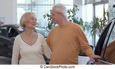 Senior couple buys the car at the dealership