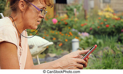 Serious mature woman in aged in glasses sits in the garden...