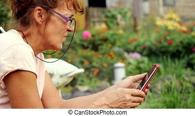 Serious pretty mature woman in aged in glasses sits in the garden on the swing uses a mobile phone.