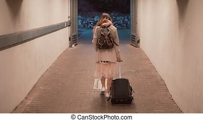 Young woman walking through tunnel carrying the suitcase....