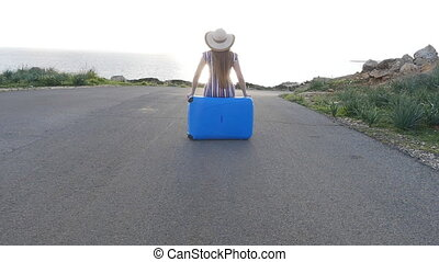 Traveler woman sitting on her suitcase waiting for the...