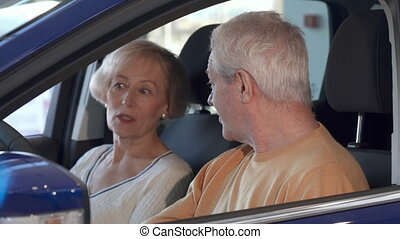 Senior couple talks inside the car