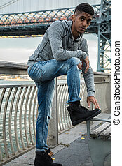 A portrait of a young, black man along NYC's East River...