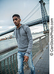A young, black man walks along NYC's East River - Autumn...
