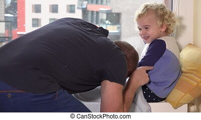 Father tickle his daughter girl sitting near window. Snow...