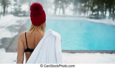 Young blonde woman in red hut goes to outdoor swimming pool...