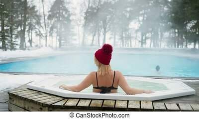 Young blonde woman in red hut in bathtub jacuzzi outdoors at...