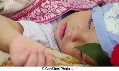 Happy cute child sleeping at flower outdoors in summer...