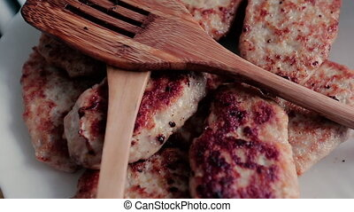 Many cutlets on a plate and wooden mixers rotate around...