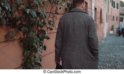 Fashionable man with backpack walking through the old street in evening. Tourist male exploring new city. Slow motion.