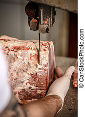 Butcher is cutting meat with bandsaw in butchery