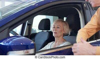 Senior couple poses with car at the dealership - Attractive...